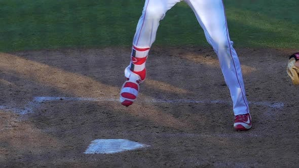 A baseball player batter makes a play at a game.