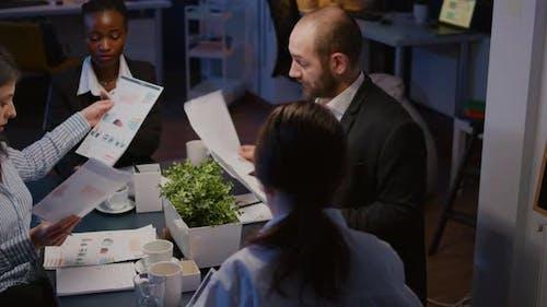 Diverse Multi Ethnic Businesspeople Sharing Management Presentation on Paperwork