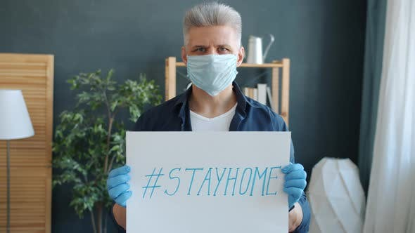 Portrait of Serious Guy in Face Mask and Gloves Holding Stayhome Banner in Apartment