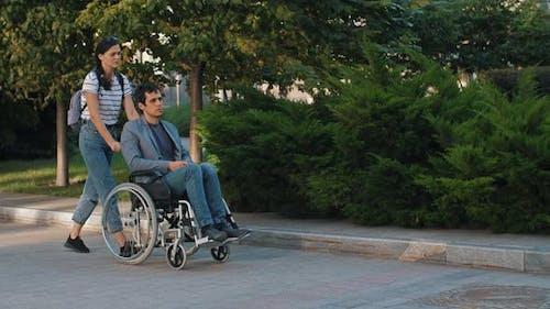 Frau schieben einen Mann in einem Rollstuhl