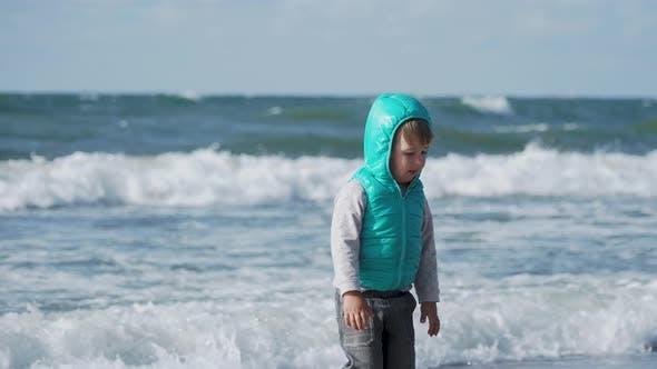Toddler Boy in Waistcoat Is Playing with Sand on Sea Side.