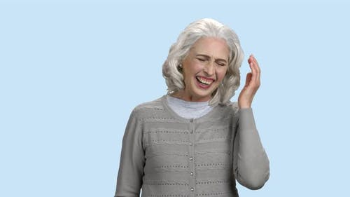 Happy Senior Woman Bursting Into Laugh.