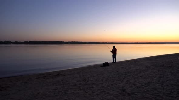 A Man Is Fishing at Sunrise By the River. The Yellow Sun Rises From the Horizon. Silhouette of a