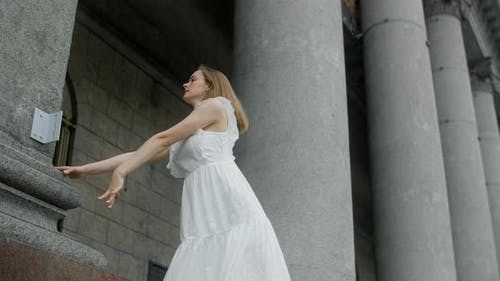 Young Balerine in White Dress Dances on the Stairs of the Theatre in Slow Motion Ballet Dancer Doing