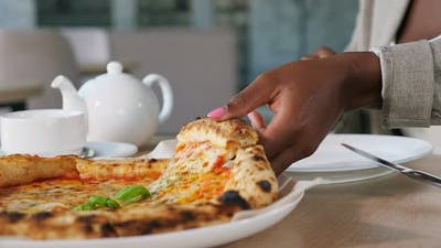 AfricanAmerican Lady Takes Slice of Pizza at Dinner in Cafe