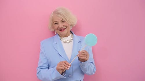 an Elderly Woman Is Surprised By a Lollipop and Smiling Poses for the Camera in the Studio, Isolated
