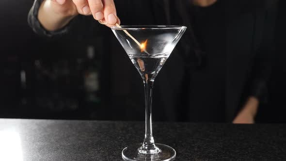 Thumbnail for Female Bartender Setting Fire with Burning Stick on Alcohol Cocktail in Slow Motion. Fire Ignition