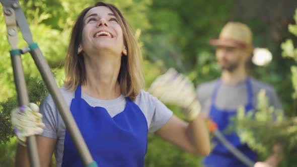 Thumbnail for Portrait of Cute Caucasian Woman Showing Thumb Up Holding Big Garden Cutter in the Foreground
