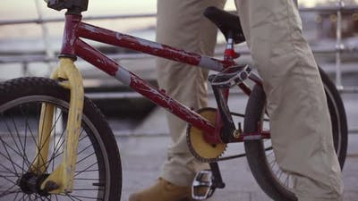 Close Up Footage of Male Ready to Ride Bmx Bicycle Standing on Pier Near Sea in Slowmotion