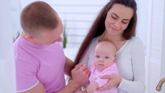 Porträt einer schönen jungen Familie mit einer kleinen Kleinkind-Tochter. Mutter hält das Baby vorsichtig in
