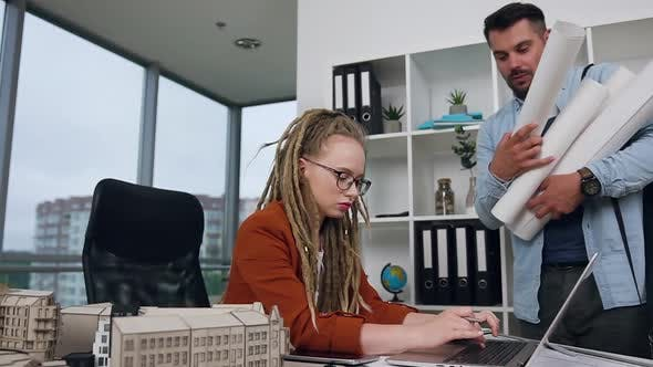 Young Designer with Blueprints Coming to His Female Boss