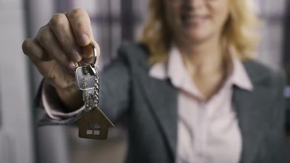 Thumbnail for Midsection of Senior Estate Agent Presenting Keys
