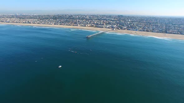 Thumbnail for Aerial shot of surfers paddling out on the ocean.