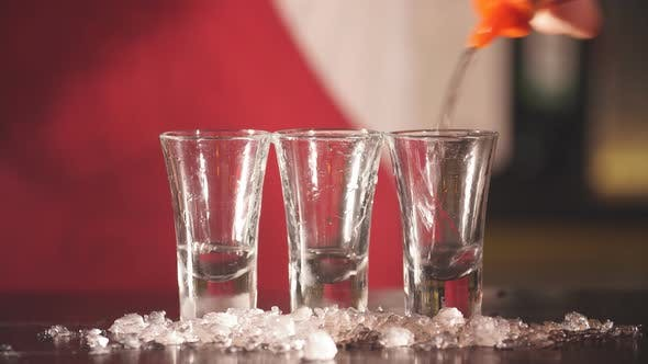 Thumbnail for Barman Hand Pours Vodka in Short Transparent Glasses with Ice Chips for Cooling