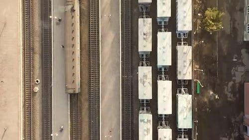 Luftaufnahme von oben nach unten vieler Güterzugwagen auf Bahngleisen.