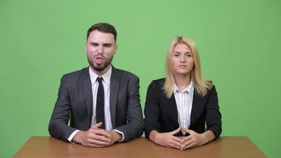 Young Businessman Making Funny Faces to Young Businesswoman