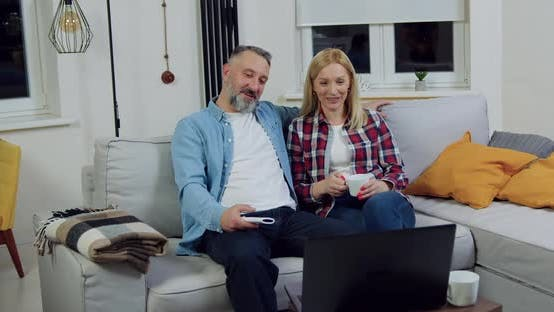 Couple which Sitting Together on Soft Couch in Living-Room and Talking