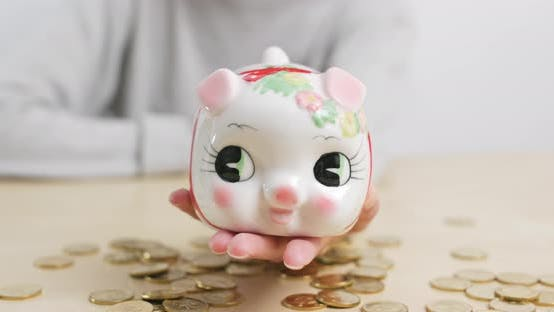 Thumbnail for Woman putting coin in piggy bank