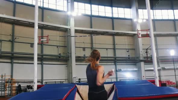 Thumbnail for Pole Vaulting Indoors - a Young Woman with Ponytail Running Up and Jumping Over the Bar - Touches