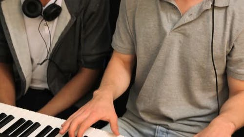 Two students playing on keyboard