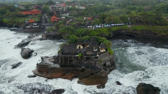 Tilting Aerial Shot Flying Away From Empty Tanah Lot Temple During Dangerous Weather in Bali