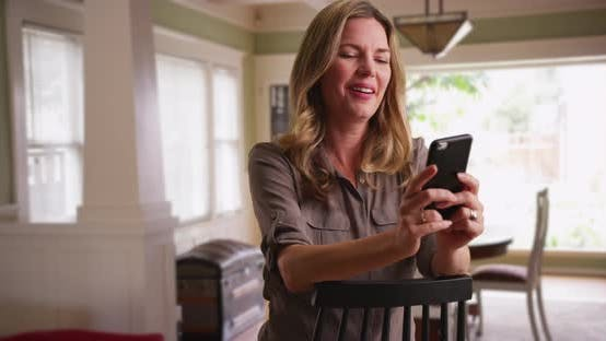 Thumbnail for Woman browsing photos on smartphone in dining room, seated in chair