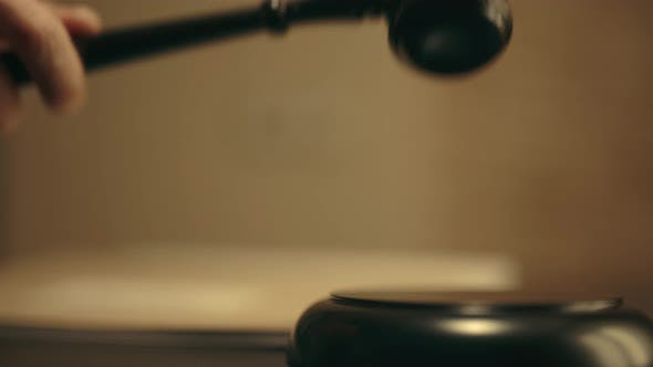 Der Richter schlägt Gavel im Gerichtssaal von einem Block