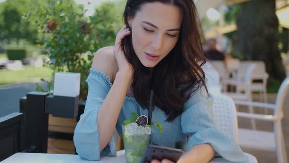 Thumbnail for Pretty Brunette Woman Sitting in Outdoor Restaurant and Using Her Mobile Phone