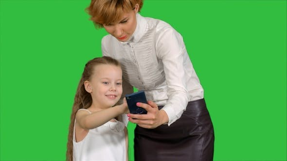 Thumbnail for Young mother teaching her daughter how to use smartphone