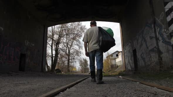 Unemployed Man Walking with Trash Bags