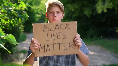a Young Caucasian Teenager in a Blue Shirt Holds a Cardboard Box with Handwritten Text BLACK LIVES