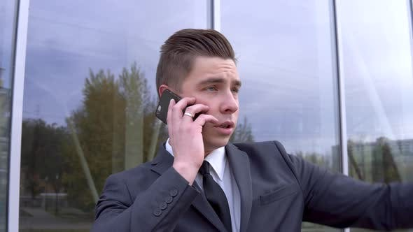 Thumbnail for A Young Businessman in a Suit Speaks on the Phone. Serious Man Stands in Front of a Mirror Business