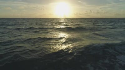 Low Level Flight Over Sea at Sunrise. Aerial Reveal Shot