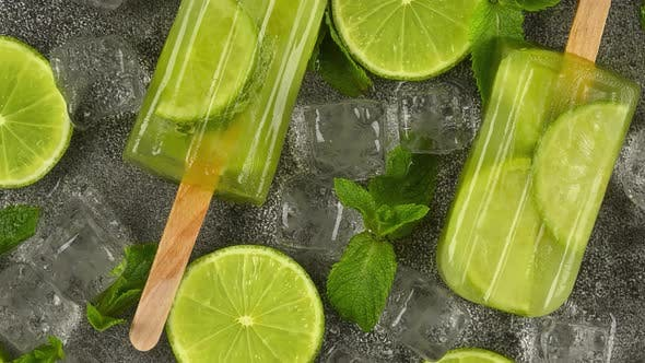 Thumbnail for Frozen fruit juice popsicles with fresh lime slices, green mint leaves and ice cubes