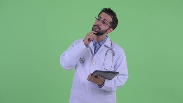 Thumbnail for Happy Young Bearded Persian Man Doctor Thinking While Using Digital Tablet