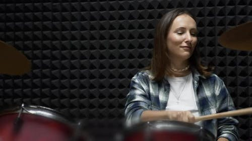 Female drums player is playing on musical instruments in dark modern rehearsal studio.