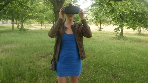 Thumbnail for Sexy Cheerful Girl Uses A Modern Virtual Reality Helmet In The Park