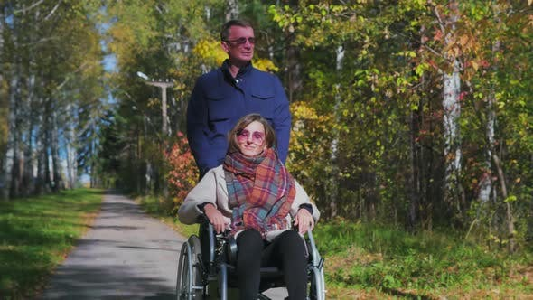 Thumbnail for Man walking with woman on wheelchair