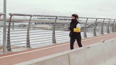 Sporty Woman Jogging on Urban Bridge in Winter