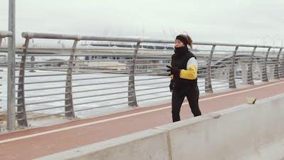 Sporty Woman Jogging on Urban Bridge in Winter