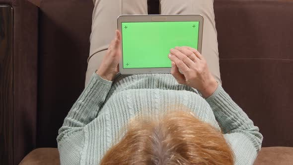 Thumbnail for Aged woman with a tablet PC (green screen) on a sofa