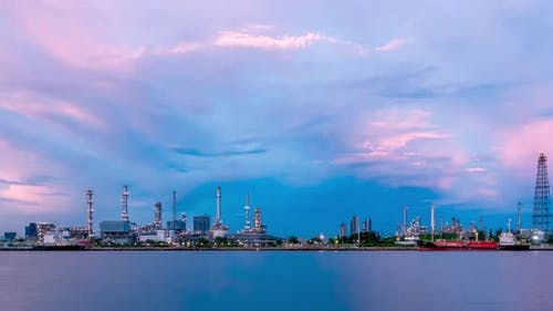Oil refinery petrochemical and energy industry, day to night, pan right - Time-lapse