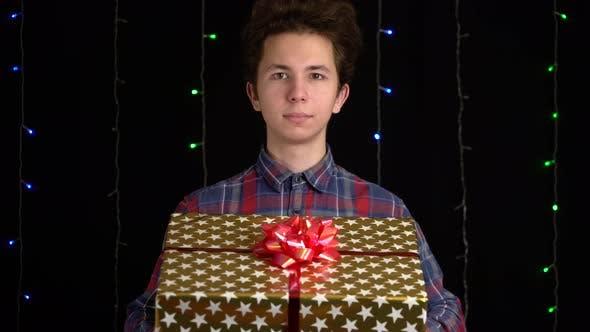 Cover Image for Junge mit einer Geschenkbox auf schwarzem Hintergrund. Geschenkbox mit Band für Frohes Neues Jahr, Frohe Weihnachten