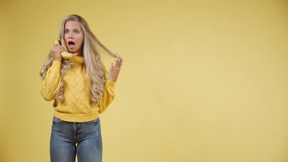 Cover Image for Playful Blonde Woman in Yellow Sweater Holding a Banana To Her Ears