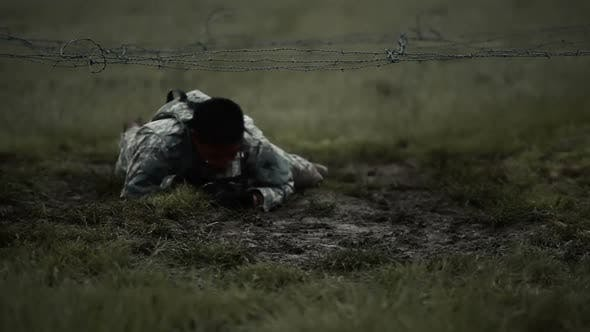 Thumbnail for Soldier crawling under low barbed wire at an obstacle course, its muddy