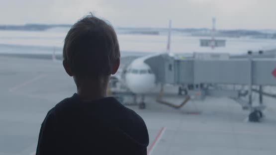 Curious Boy Looks Out of Panoramic Window at Large Airplane