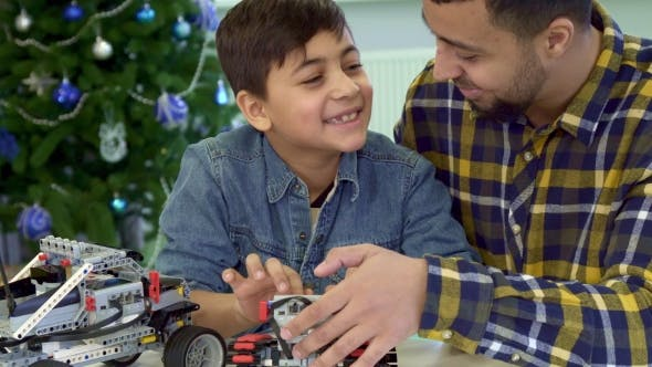 Cover Image for Father and Son Examine Toy Tracked ATV