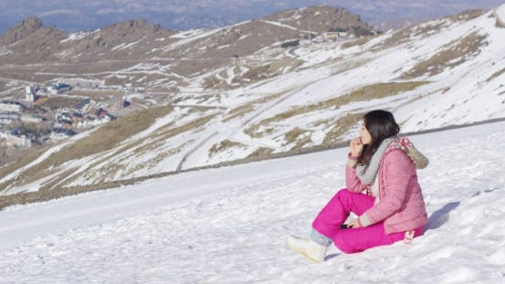 Young Woman on Snowy Mountain Summit