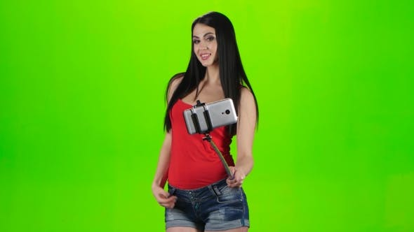 Thumbnail for Girl Doing Selfie Using a Smartphone Fixed on the Monopod