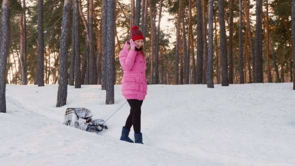 Thumbnail for Young Woman in Pink Down Jacket Carries a Sled in the Winter Woods